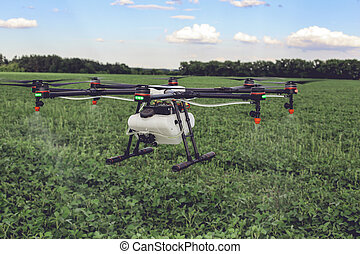 Agriculture drone fly to sprayed fertilizer on the green fields.