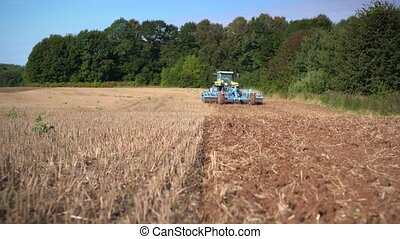 Agriculture machine discing stubble field. Walking toward ...