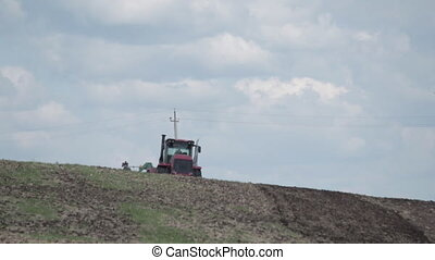 Agriculture machine spread fertilizer on cultivated field soil in summer. Planting crops. blue sky