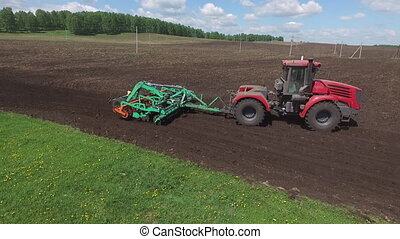 Agriculture machine tractor plow and spread fertilizer on cultivated field soil in summer. Planting crops