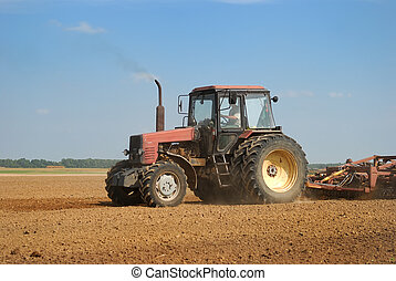 Agriculture tractor in yellow field outdoors in summer with plough
