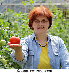 Smiling caucasian woman holding tomato in hand, selective focus on tomato