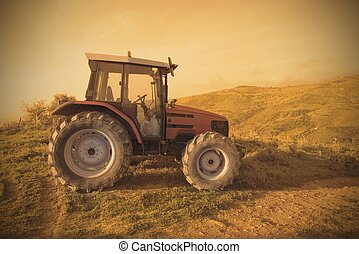Tractor in a field during sunset