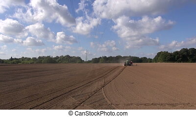 Agriculture tractor sowing wheat seeds in field on sunny...