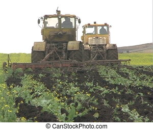 Agriculture - Two tractors plow the field.