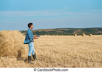 Agronomist farmer in jeans, shirt with a tablet is in the field with a stack, with tablet looking into the distance. Rural business, agricultural industry, freedom after work, concept