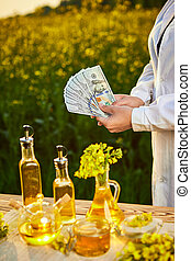Agronomist woman or farmer holding money dollar banknote with blossoming cultivated canola field and rapeseed oil in background