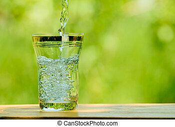agua que vierte, en, un, vidrio, contra, el, verde, naturaleza, plano de fondo