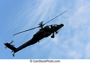 An AH-64 Apache helicopter turns against a blue sky