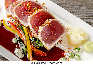 Close up of rare seared Ahi tuna slices with bok choy stir fry vegetables and wasabi peas on white plate