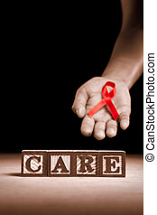 Word 'Care' from wooden block with hand holding red ribbon on dark background