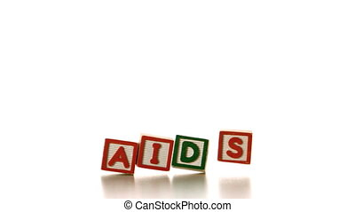 Aids spelled out in blocks falling over in slow motion