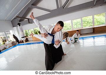 Aikido teacher doing throw with girl wearing white kimono - ...