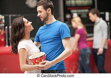 aimer couple, à, les, cinema., gai, jeune couple, étreindre, et, regarder autre, quoique, debout, à, les, cinéma, salle