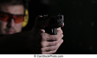 Aiming a gun on black background - Holding a pistol over...