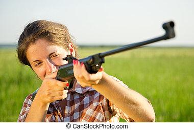 aiming girl - girl aiming a pneumatic rifle against summer...