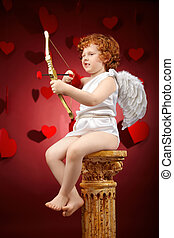Aiming - Small aiming boy in an image of the cupid on a red...