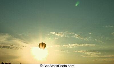 Air balloon cross the sun on the sunset