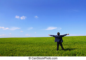A man alone in a green field, breathing the air with open arms