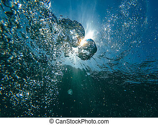 air bubbles at water surface in sea in clear blue water