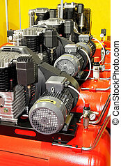Air compressors - Several red powerful air compressors in...