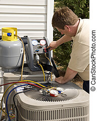 Vertical shot of an air conditioning repairman working on a unit.