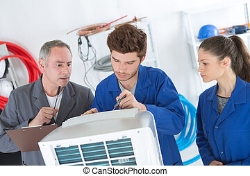 air conditioning repairmen discussing the problem with a compressor unit