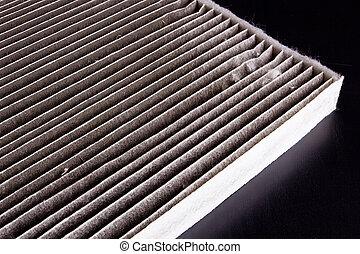 Air filter car - A dirty air filter car on a black table.
