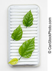 air filter purity concept with three fresh green leafs on...