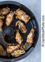 Air fried chicken wings in an air fryer. Close up of tasty air fried chicken wings on a grey background.