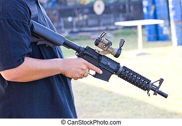 Air gun in Asian man's hand.