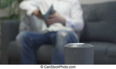 Air humidifier at living room. Man reading book on the...
