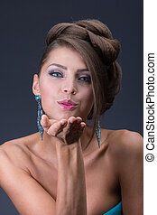 Air kiss from Woman wearing shiny blue earring