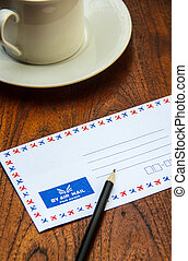 Air mail envelope with pencil and coffee cup