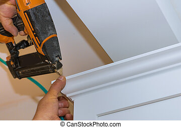 Air nailer tool carpenter using nail gun to crown moldings...