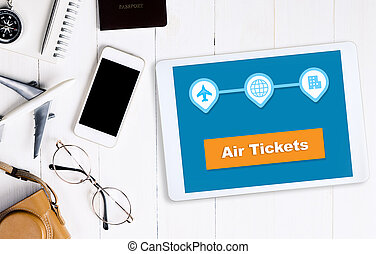 Air plane booking application on tablet screen with travel accessories