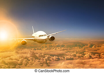 air plane flying over cloud scape and sun light behind