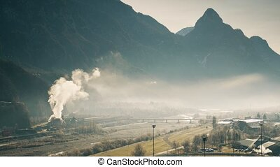 Air polluting facility in the river valley, northern Italy...