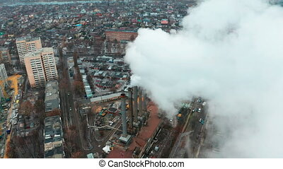 Flying a drone through white clouds of thick smoke from industrial pollution of the atmosphere - a concept of air pollution from industrial human activities.