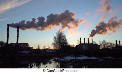 Air pollution from industrial plant pipes.