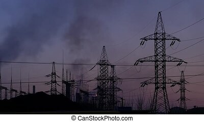 Air pollution from industrial plants. Pipes throwing black smoke on a evening sky. hanging wires and electric supports
