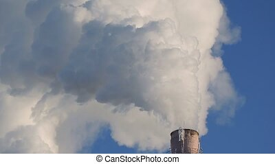 Air pollution from the plant. Smoke and pipes on background of blue sky