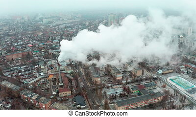 Tilt and pan Flying a drone through white clouds of thick smoke from industrial pollution of the atmosphere - concept of air pollution from industrial human activities in the city.