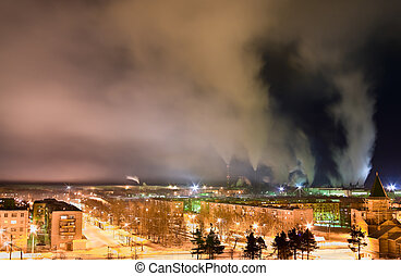 Smoke from chimneys over a town at nighttime. Night scene. Long exposure.