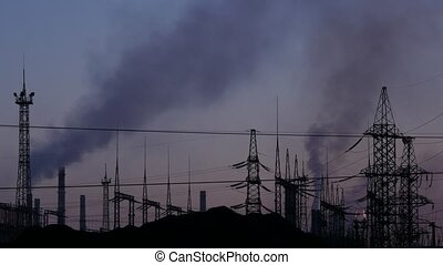 Air pollution. Pipes throwing black smoke on a evening sky. hanging wires and electric supports.