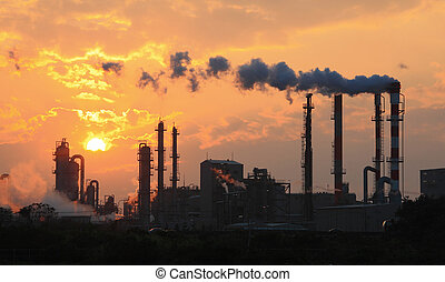 Air pollution smoke from pipes and factory with sunset...