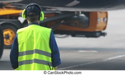 Air runway signalman, marshaller in reflective vest