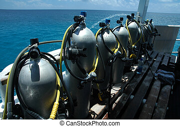 air tanks - several scuba cylinders on boat, ocean in ...