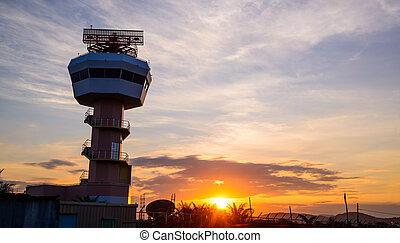 Air traffic control tower over sunset