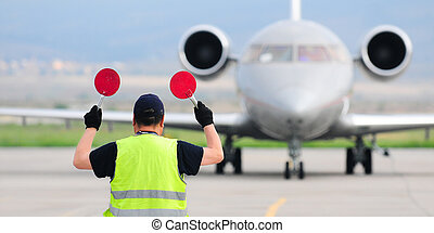 Air traffic controller holding signs at the airport
